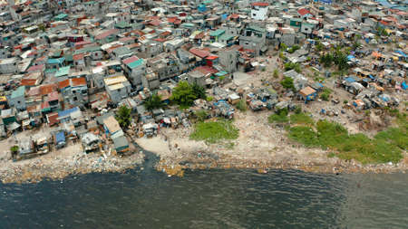 Slums near the port in Manila on the bank of a river polluted with garbage, aerial view.