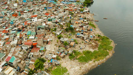 Slums in Manila on the bank of a river polluted with garbage, aerial view. Stock Photo - 129598922
