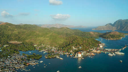 sea port, pier, cityscape Coron town with boats on Busuanga island, Philippines, Palawan. Coron city with slums and poor district. Seascape with mountains.