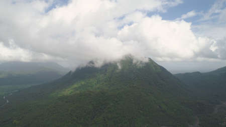 Aerial view of mountains covered forest, trees in cloudy weather, Bulusan Volcano. Luzon, Philippines. Slopes of mountains with evergreen vegetation. Mountainous tropical landscape.