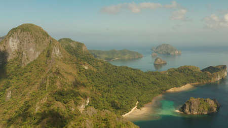 Cove with tropical rocky islands covered with rainforest, sea with blue water, aerial view. El nido, Philippines, Palawan. Tropical Mountain Range