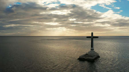Catholic cross in sunken cemetery in the sea at sunset, aerial drone. Large crucafix marking the underwater sunken cemetary, Camiguin Island Philippines. Stok Fotoğraf