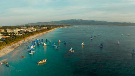 Aerial view of sailing boats on the sandy beach of Boracay Island at sunset time. Tropical white beach with sailing boat. Summer and travel vacation concept.