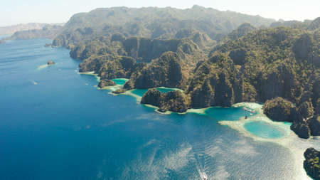 Tourist boats around the beautiful big and small lagoons, aerial view. lagoon, mountains covered with forests.coves with blue water among the rocks. Seascape, tropical landscape. Palawan, Philippines Stok Fotoğraf