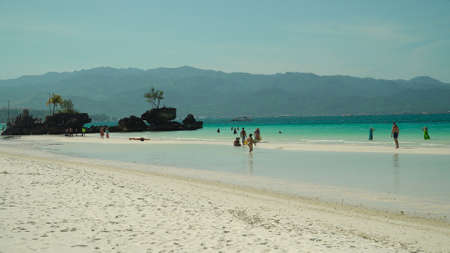Topical white beach and Willys rock with tourists on Boracay Island. Summer and travel vacation concept.
