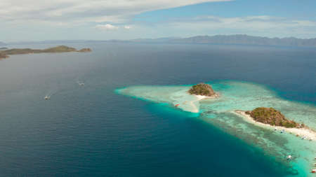 aerial seascape bay with tropical island and sand beach, turquoise water and coral reef. Bulog Dos, Philippines, Palawan. tourist boats on coast tropical island.