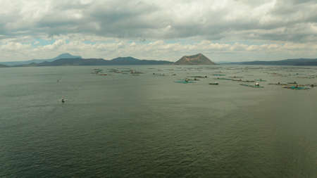 Taal volcano on an island in middle lake with fish farm, aerial view. Luzon, Philippines Tropical landscape, mountains and volcano in the lake.