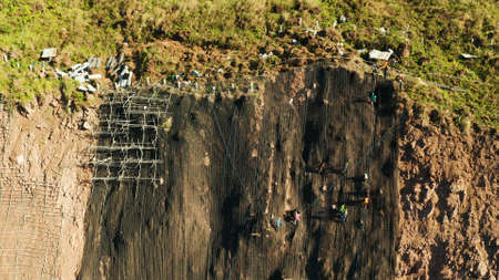 Workers strengthen the slope of the mountain with metal mesh preventing rockfall and landslide on the road, above view. workers constructing anti-landslide concrete wall prevent protect against rock slides. safety concept Stok Fotoğraf