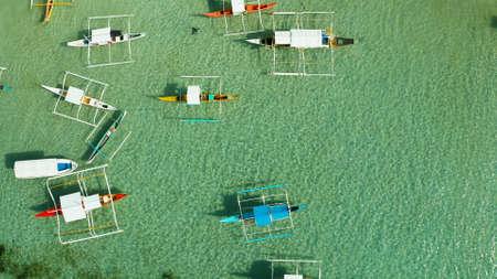 Embarcaciones a motor en agua azul en una playa tropical, vista aérea. Concepto de vacaciones de verano y viajes.