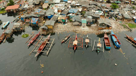 Slums with shacks of local residents and the river bank littered with garbage from above. Manila, Philippines. Stock Photo