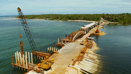Pile hammer working on construction site. Bridge under construction over the sea bay connecting the two parts of Siargao island. Archivio Fotografico