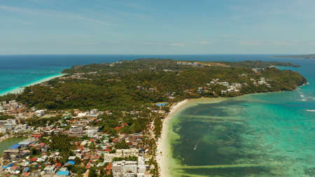 Shore of the tropical island of Boracay with sandy beaches and hotels from above. Summer and travel vacation concept. Philippines.