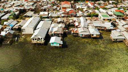 Fishing village with boats and slums with wooden houses, aerial drone. Dapa, Siargao, Philippines.