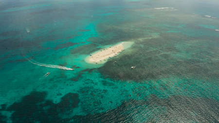 Tropical white island and sandy beach with tourists surrounded by coral reef and blue sea, aerial view. Naked Island, Siargao. Summer and travel vacation concept Stok Fotoğraf