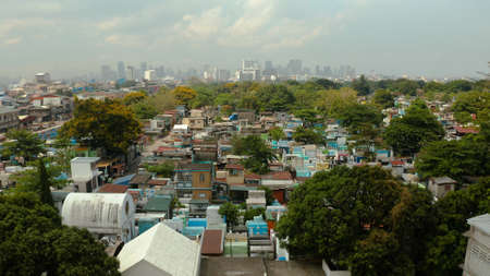 The city of Manila, the capital of the Philippines and Manila North Cemetery, top view. Modern buildings in the city center. Stok Fotoğraf