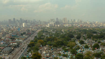 Aerial view of panorama of Manila North Cemetery with skyscrapers and business centers in a big city. Travel vacation concept