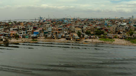 Slum area near the port in Manila, Phillippines, top view. lot of garbage in the water.