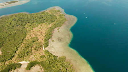 Tropical island with mangroves surrounded by a coral reef and blue sea. aerial view Stok Fotoğraf