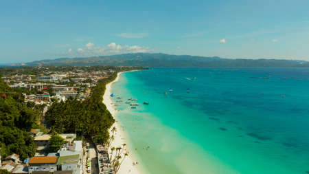 Tropical lagoon with turquoise water, sailing yachts and white sand beach from above. Boracay, Philippines. White beach with tourists and hotels. Summer and travel vacation concept.