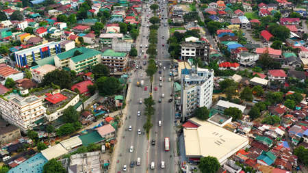 Highway with heavy traffic in Manila, aerial view. Streets and houses with dense buildings in the city of Manila, Philippines. Travel vacation concept.