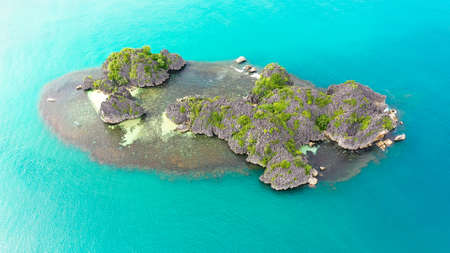 Tropical island with sandy with tourists and blue sea, aerial view. Caramoan Islands, Philippines. Summer and travel vacation concept.