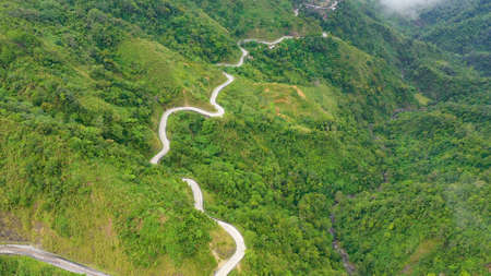 Fragment of a high altitude road in the mountains. Mountains covered by rainforest, aerial view. Cordillera on Luzon Island, Philippines.