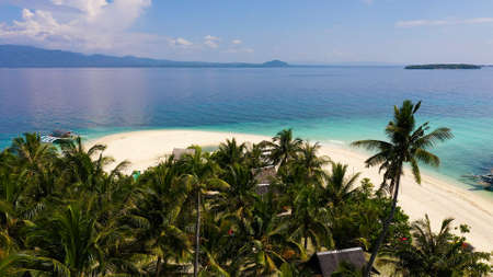 Beautiful beach. View of nice tropical beach with palms around. Holiday and vacation concept. Tropical beach. Digyo Island, Philippines.
