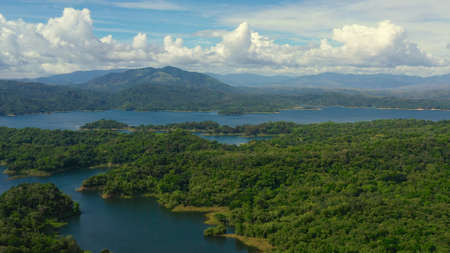 Clouds over a blue lake among green hills and mountains covered with rainforest. Aerial view: Pantabangan Lake. Philippines, Luzon.
