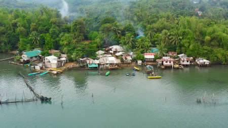 Fishing village with wooden houses standing on stilts in the sea from above. Houses community standing in water in fishing village. Luzon, Philippines.