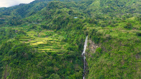 Mountain landscape with rainforest and waterfall, aerial view. Highlands with villages on the island of Luzon, Philippines.