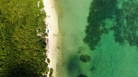 A lagoon with a coral reef and a white sandy beach, aerial drone. The coast of a tropical island. Caramoan Islands, Philippines. Summer and travel vacation concept.