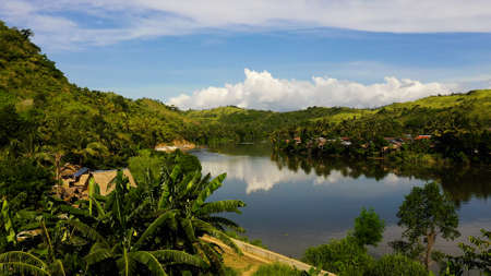 River and green hills. Beautiful natural scenery of river in southeast Asia. Countryside on a large tropical island. Small village on the green hills by the river. The nature of the Philippines, Samar