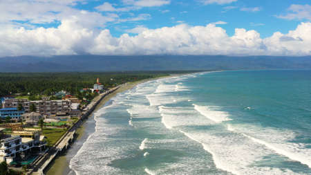 Sandy beach and ocean waves, aerial view. Coastline with hotels and tourists. Surfers in the water. Sabang Beach, Baler, Aurora, Philippines. Summer and travel vacation concept.