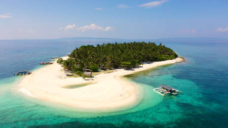 The island of white sand on a large atoll, view from above. Tropical island with palm trees. Seascape with a paradise island. Digyo Island, Philippines. Summer vacation and tropical beach concept.