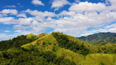 Mountain landscape with green hills and mountains with forest.Mountain valley and blue sky with clouds. Philippines, Luzon. Summer landscape.