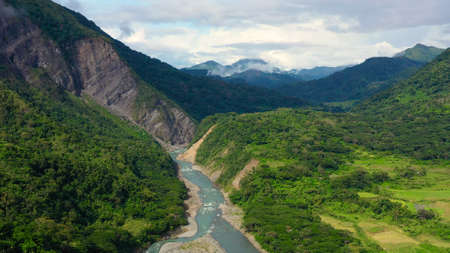 Mountains covered by rainforest, aerial view. River in a mountain gorge. Cordillera on Luzon Island, Philippines. Summer and travel vacation concept.