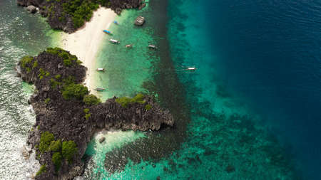 Tropical beach with tourists surrounded by blue water, aerial view. Lahos Island, Caramoan Islands, Philippines. Summer and travel vacation concept. Zdjęcie Seryjne