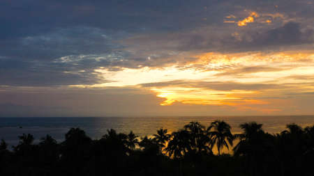 Sunrise on a tropical island with palm trees. Tropical island during sunrise.Early morning in the tropics. Philippines, Anda, Pangasinan. Travel concept.