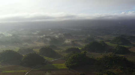 Tropical landscape with farmland and green hills, aerial view. The nature of Luzon Island, Philippines. Fog in the early morning.