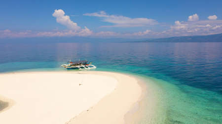 Perfect beach with blue water and white sand. Boat off the coast of a tropical island. Summer and travel vacation concept. Digyo Island, Philippines. Holiday and vacation concept.