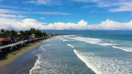 The city of Baler in the Philippines, known as the capital of surfing. Wide beach with big waves and surfers. Sabang Beach, Baler, Aurora, Philippines. Summer and travel vacation concept.