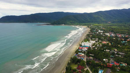Sandy beach with hotels and tourists, spot of surfing. Aerial drone: Sabang Beach, Baler, Aurora, Philippines. Summer and travel vacation concept. Banque d'images