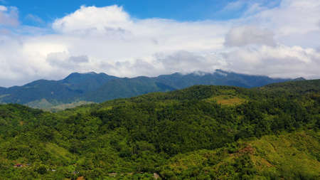 Hills and mountains covered with green grass and rainforest against a background of blue sky and clouds. Philippines, Luzon. Summer landscape. Banque d'images
