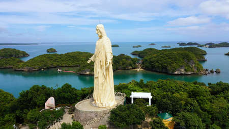 Sculpture of Jesus Christ on an island located in a Hundred Islands National Park, Pangasinan, Philippines. Aerial drone: cluster of Islands with beaches and lagoons, famous tourist attraction, Alaminos. Banque d'images