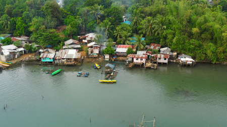 Fishing village with boats and slums with wooden houses, aerial drone. Houses community standing in water in fishing village. Luzon, Philippines.