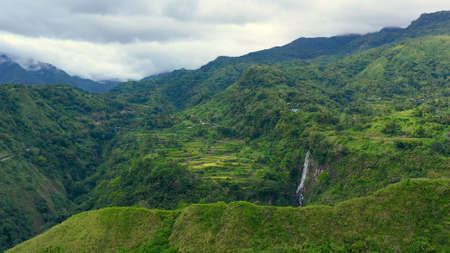 Highlands with villages on the island of Luzon, Philippines. Mountains covered with jungle and a waterfall in the distance, aerial view.