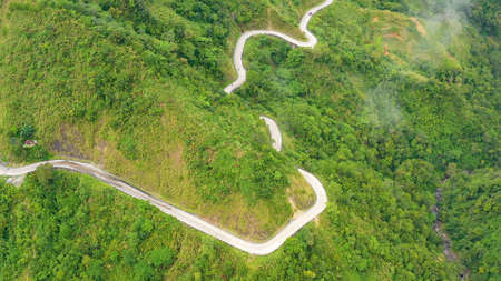 Mountain curve road passing along the slopes of mountains and hills covered with green forest and vegetation. Philippines, Luzon. Mountains covered by rainforest, aerial view.