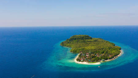 Himokilan Island, Leyte Island, Philippines. Tropical island with a village and a white beach. Turquoise water and coral reefs around the island. Summer holiday vacation concept.