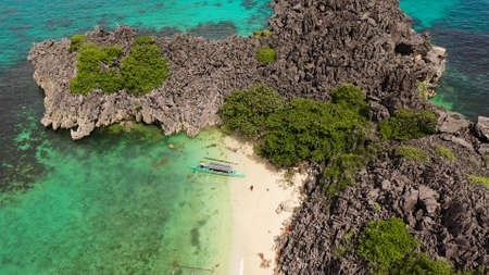 Sandy beach with tourists and tropical island by atoll with coral reef, top view. Matukad Island, Caramoan Islands, Philippines. Summer and travel vacation concept. Rocky island with a small beach. Banque d'images