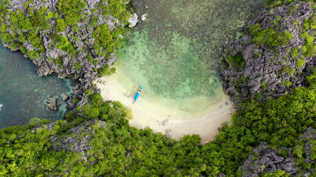 Tropical islands and blue sea, aerial view. Kagbalinad Islands, Philippines. Rocky islands with trees. Summer and travel vacation concept. Rocky island with rainforest